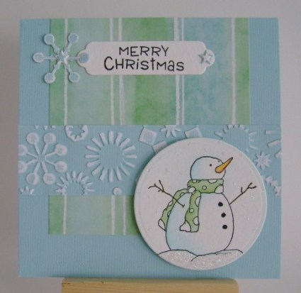 snowman with green scarf on blue and green papers