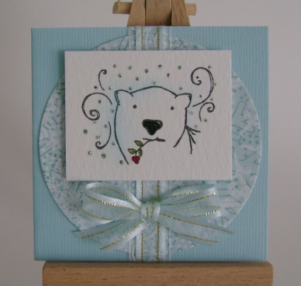 polar bear in front of blue card with blue ribbon