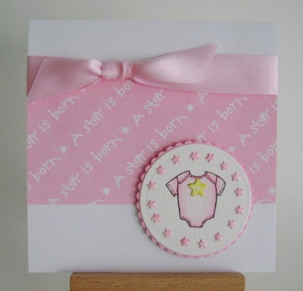 pink baby onesie with a star is born paper