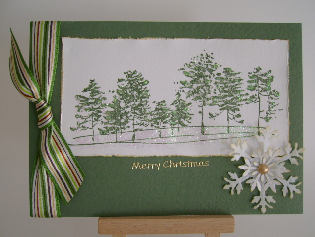 row of green trees in snow with striped ribbon and snowflake