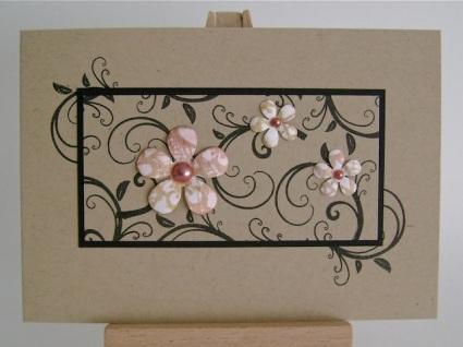 black swirls on kraft paper with three pink flowers