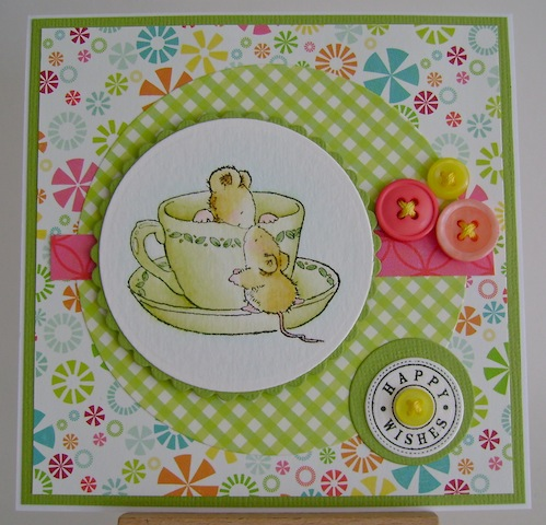two mice on a green teacup and saucer with summer colours in papers
