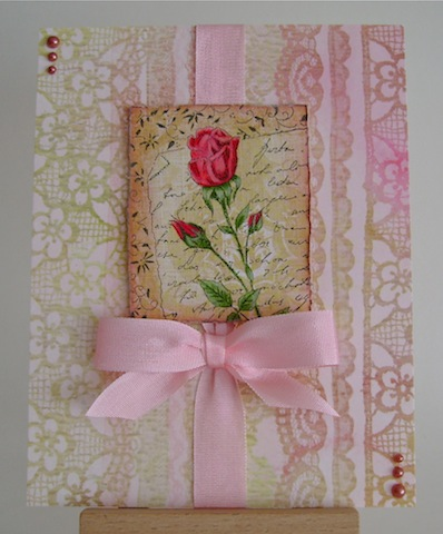 red rose on pink and beige lace paper with pink ribbon and pearls