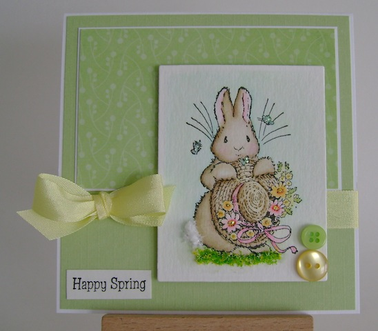 bunny holding straw hat with flowers and butterflies floating nearby