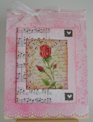 red rose in front of text, musical notes and stamped hearts in pink