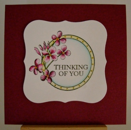 circle framed flowers on berry coloured square card base
