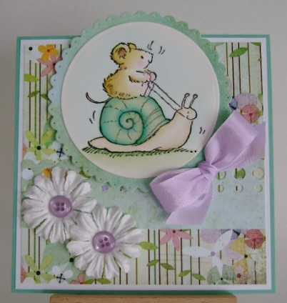 mouse riding aqua coloured shell with white flowers and purple bow