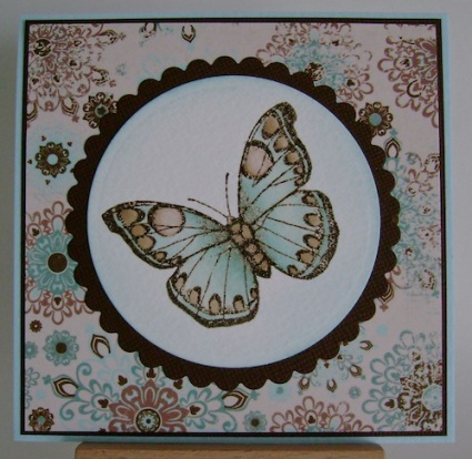 blue and brown butterfly on circle matted with brown against blue and brown designer paper