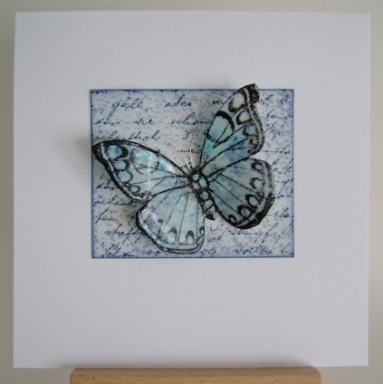 blue butterfly on top of blue paper with blue text on square white card