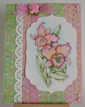 pink and yellow orchid on pink and green designer floral paper with pink bow and pink pearls