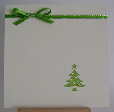 tiny punched green christmas tree in bottom right corner with green ribbon and bow at top left of card