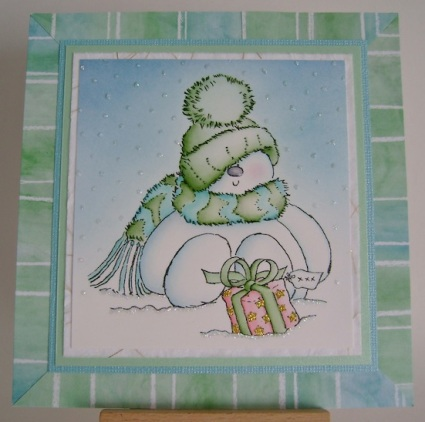 snowgirl wearing green hat with blue and green scarf on striped bue and green framed card