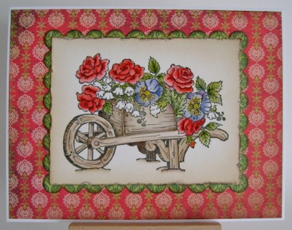 wheelbarrow full of red rose, purple pansies and white lily of the valley flowers