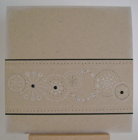 white stamped snowflakes with black trim and three black gems on kraft card
