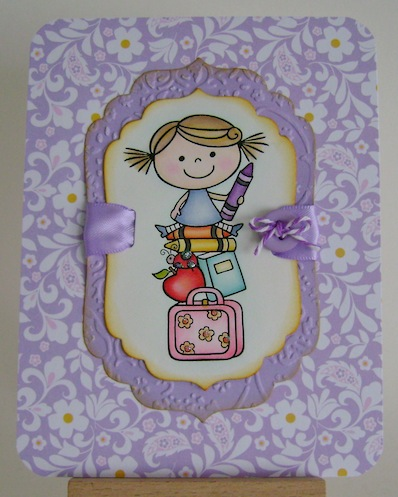 card with digital image of girl sitting atop crayons, book, apple with purple floral background