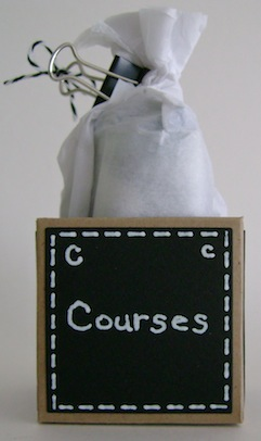 little box with the word courses in white text on black paper