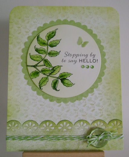 a green monochromatic card with leaves, twine, button and a stopping by to say hello sentiment