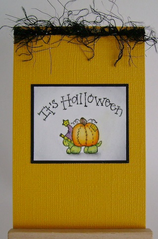 an orange card with black fuzzy ribbon at the top, a turtle carrying a pumpkin on its back and a sentiment that reads it's halloween