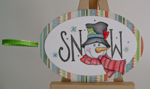 snowman gift tag with green ribbon and striped paper frame
