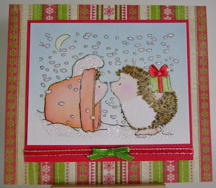 two hedgehogs at christmas, one in a clay pot and one holding a present behind its back