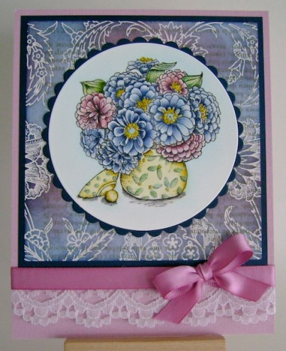 blue and pink floral bouquet with pink bow and lace trim on bottom of card