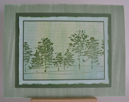 green card with blue frame and row of green trees