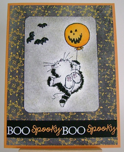 card with scared black cat hanging on to jack o lantern balloon with three bats nearby