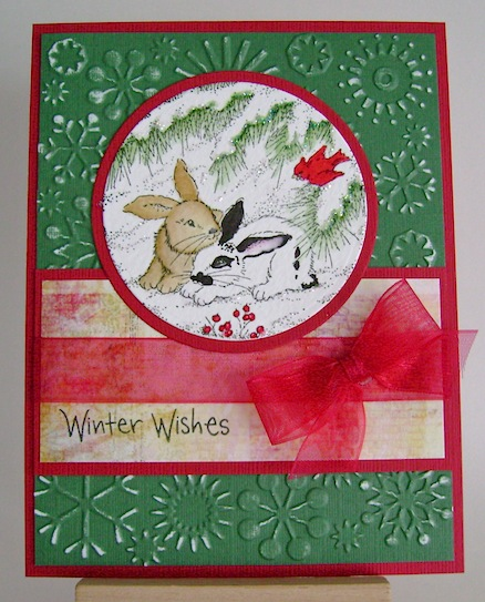 christmas card featuring two bunnies under an evergreen tree with red bow