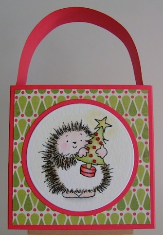 red tote bag with hedgie carrying a christmas tree image on the front