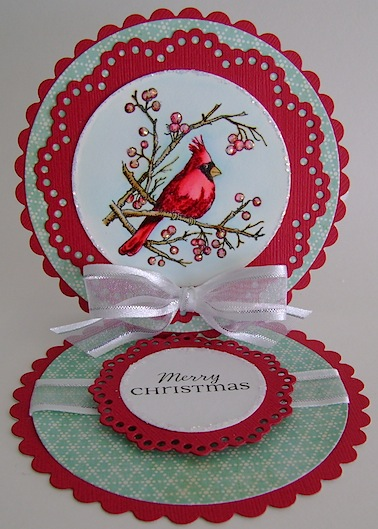 red circle easel christmas card featuring a red cardinal with glitter and white bow
