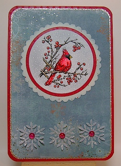 blue greeting card featuring red cardinal in tree branches and snowflakes