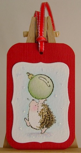hedgehog carrying green christmas ornament