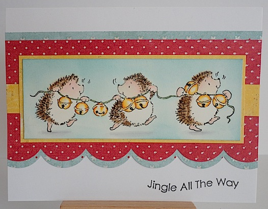 christmas card with three hedgehogs carrying a string of jingle bells
