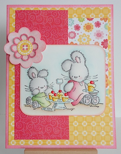 card with two lili of the valley bunnies and a plate of cupcakes in pinks and yellows