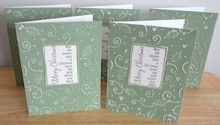five christmas cards in green and white with embossed holly and swirls