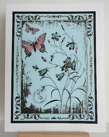 card with floral image and butterfly stamped on blue vellum with a touch of pink ink