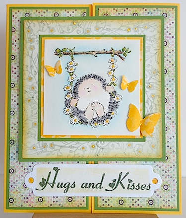 card in green, white and yellow with hedgehog on a swing and hugs and kisses sentiment
