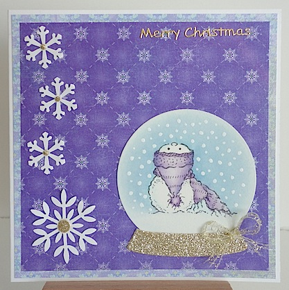 christmas card with snowman in snow globe with purple toque and purple papers with white snowflakes