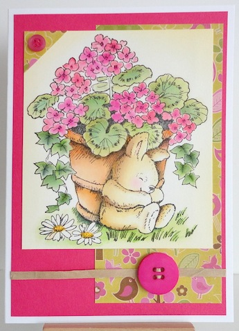 card with pot of pink geraniums and sleeping bunny next to the pot on the ground