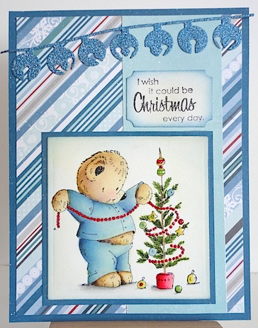 christmas card with teddy in blue pyjamas decorating a tree; background papers are blue diagonal stripes with white and red plus a die cut strand of blue glitter jingle bells