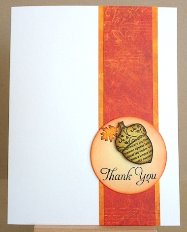 thank you card with acorn and oak leaf on a circle against a strip of orange and gold paper on a white card stock base