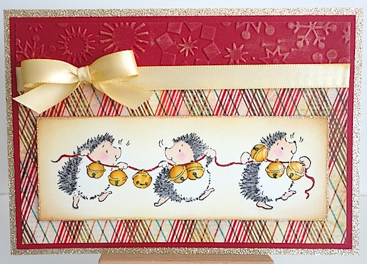 christmas card with three hedgies running along carrying a string of jingle bells on and red and brown plaid background with red card stock and gold bow