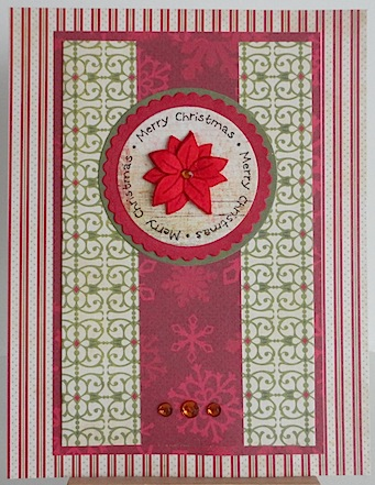 christmas card in red and green with red poinsettia and merry christmas circular sentiment