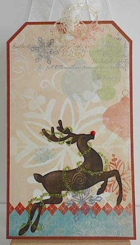 christmas tag with reindeer and snowflakes in the background in blues, green and rust colours