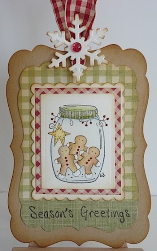 tag in red, green and brown with jar of gingerbread cookies, a season's greetings sentiment with a red check bow at the top with a white snowflake sponged brown on the edges and red gem in the middle