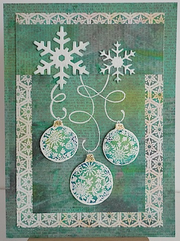 christmas card in green and white with three ornaments dangling from two die cut snowflakes