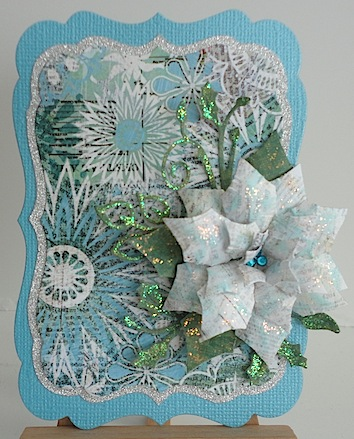 christmas card in blue, green and white with white and blue poinsettia and glitter