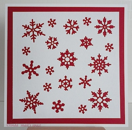 a square christmas card with red snowflakes on white background
