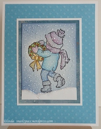 christmas card with boy walking through snow and carrying a wreath