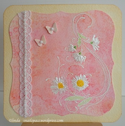 card with white daisies on a pink background with lace and pearls and two tiny butterflies